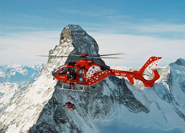 Air Zermatt helicopter with mountain rescuer on the longline; in the background, the Matterhorn.