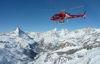 Helikopter der Air zermatt im Anflug nach Zermatt. Im Hintergrund das Matterhorn (links).