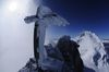 A cross stands on the rocky summit of the Nadelhorn.