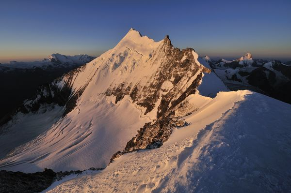 The Weisshorn at sunset, its glaciated slopes glowing pink.