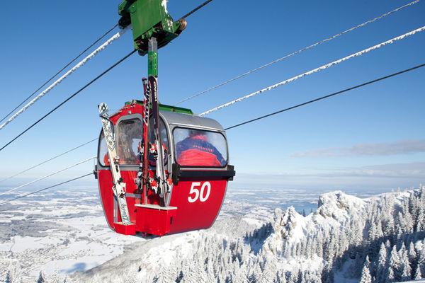 Rote Bergbahnkabine hoch über der Kampenwand. Blauer Himmel und weiße Bergspitzen.