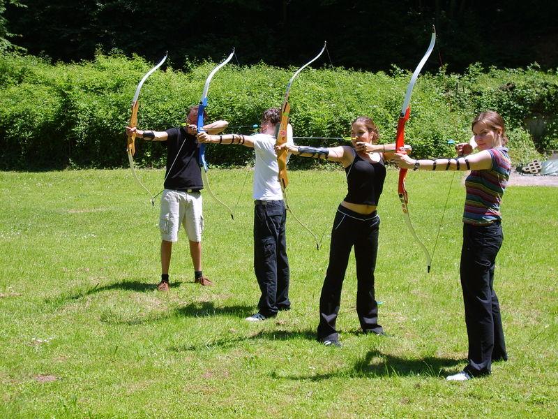 vier Erwachsene beim Bogenschießen