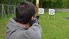 Junge zielt mit dem Bogen auf Zielscheibe