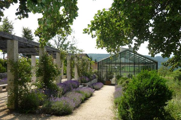 Links ein Säulengang. In der Mitte führt ein Weg zwischen Blumenbeeten zu einem Gewächshaus, der Orangerie in Bad Endorf.