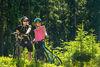 Zwei Fahrradfahrerinnen stehen neben ihren Fahrrädern im Wald und schauen in die Ferne