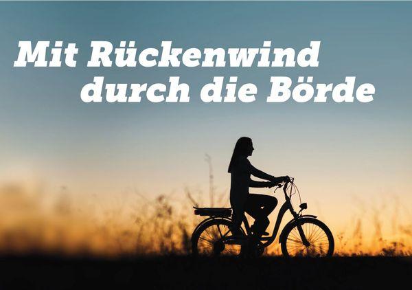 Silhouette einer Frau auf einem Rad, die bei Sonnenuntergang am Rand einer Wiese Fahrrad fährt.