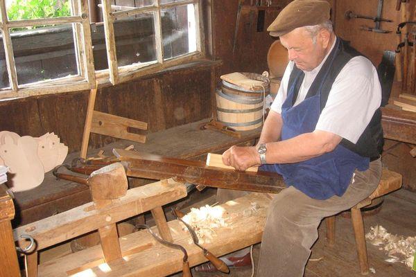 """Bernau: Holzhandwerker auf dem """"Schnidesel"""" - auf dem Schneidestuhl wird das Holz eingeklemmt und mit einem Ziehmesser bearbeitet."""