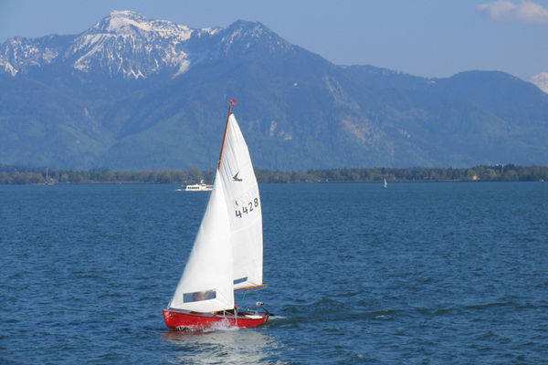 Segelboot auf dem Chiemsee vor toller Alpenkulisse.