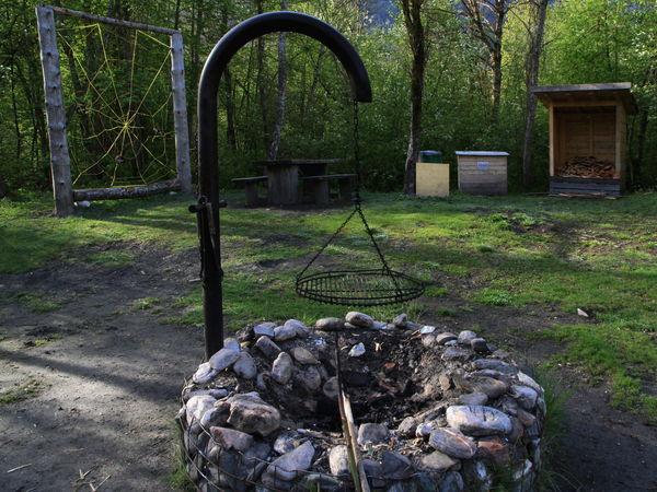 Grill im Hintergrund eine Wiese und die Holzaufbewahrung.