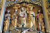 Im Schrein sind neben Maria mit dem Kind auf der linken Seite Johannes der Täufer mit einer Bibel und dem Lamm und der heilige Sebastian als modischer Ritter