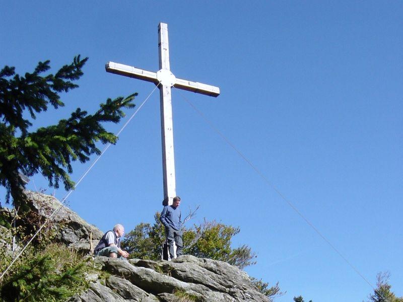 Wanderer beim Gipfelkreuz auf dem Dreitannenriegel im Bayerischen Wald