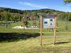 Infotafel am Erlebnisweg Falke mit Blick auf den Kinderspielplatz beim Glasmuseum Frauenau