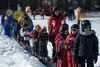 Skischullehrer mit den Kinder auf dem Zauberteppich