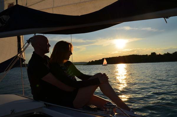 Segler beobachten den Sonnenuntergang am Chiemsee vom Schiff aus.