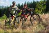 zwei Mountainbiker schieben ihr Fahrrad über eine Waldwiese
