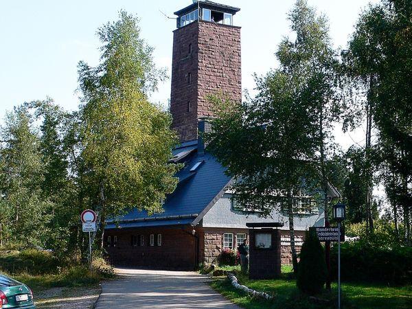 Gasthaus mit Aussichtsturm umgeben von Bäumen