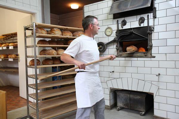 In der Backstube steht der Müller vor dem Backofen und schiebt Brot mit einem langen Brotschieber hinein. Links daneben steht ein mehrstöckiges Holzregal auf welchem die fertigen Brote abgelegt werden.