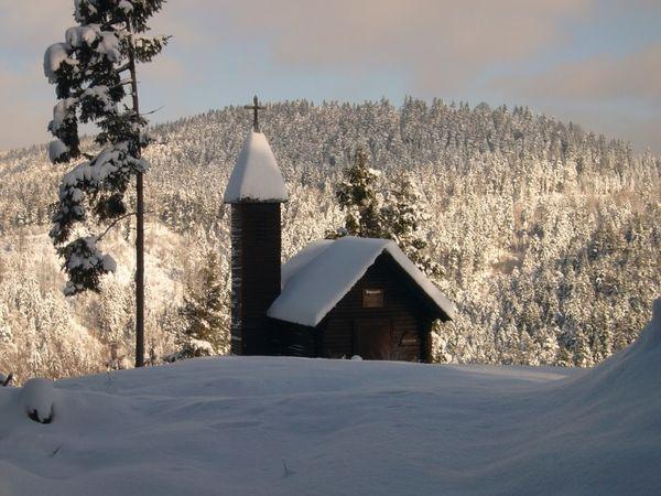 Kleine Rundholzkapelle mit Glockenturm im Winter und Blick über den verschneiten Wald.