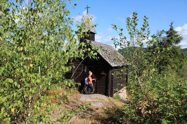 Kleine Rundholzkapelle mit Blick über Lauterbach. Rechts und links davon stehen Bäume. Eine Frau öffnet die Tür.