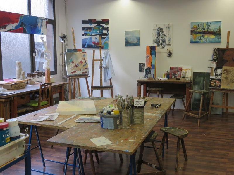 Ein Blick ins Atelier mit seinen Arbeitstischen, Staffeleien und fertigen Bildern an den Wänden.