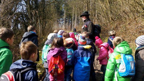Eine Gruppe Kinder lauscht auf einem Waldweg den Erklärungen eines Mitarbeiters der Waldschule