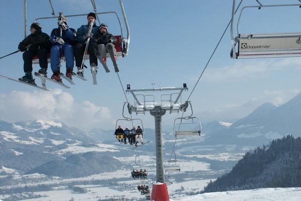 Bergbahn Hocheck im Winter. Skifahrer werden mit dem Sessellift nach oben befördert. Winterliches Alpenpanorama.