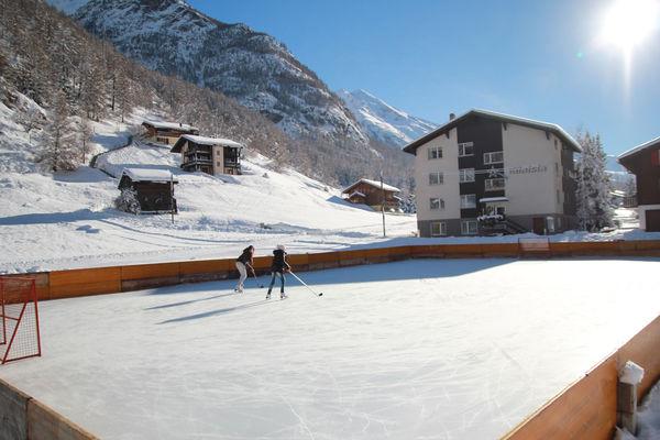 Plaisir sur glace: jouer au hockey ou exécuter des pirouettes au cœur du village, face à des montagnes majestueuses.