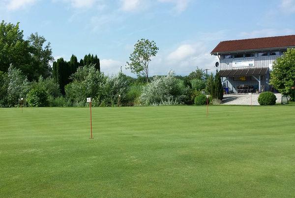 Golfplatz mit Clubhaus im Hintergrund.