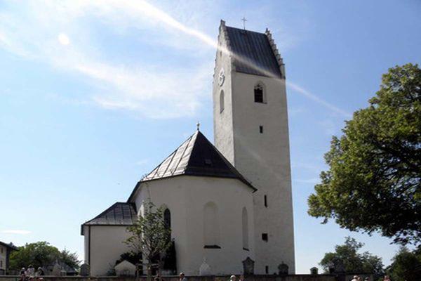 Zaunblick auf die Kirche Sankt Bartholomäus in Roßholzen