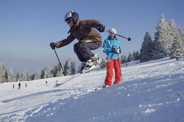 Mädchen in Skiausrüstung springt über eine Sprungschanze.