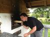 Wastl zu Besuch im Hotel Gut Schmelmerhof - Wastl heizt dem Backofen in Garten ein
