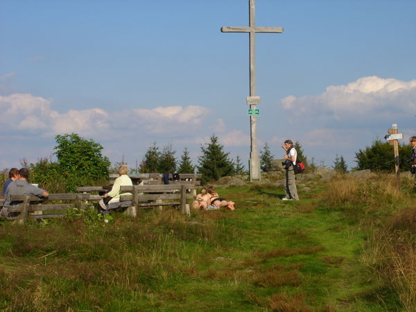Wanderer rasten nach dem Aufstieg am Pröller-Gipfelkreuz bei St. Englmar im Bayerischen Wald