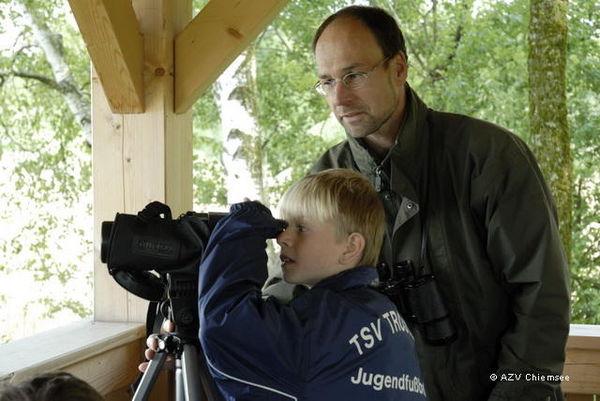 Junge wirft unter Anweisung des Lehrers einen Blick durch das Fernrohr im Turm.