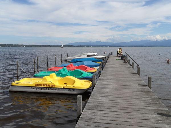 Steg in den Chiemsee mit Booten.