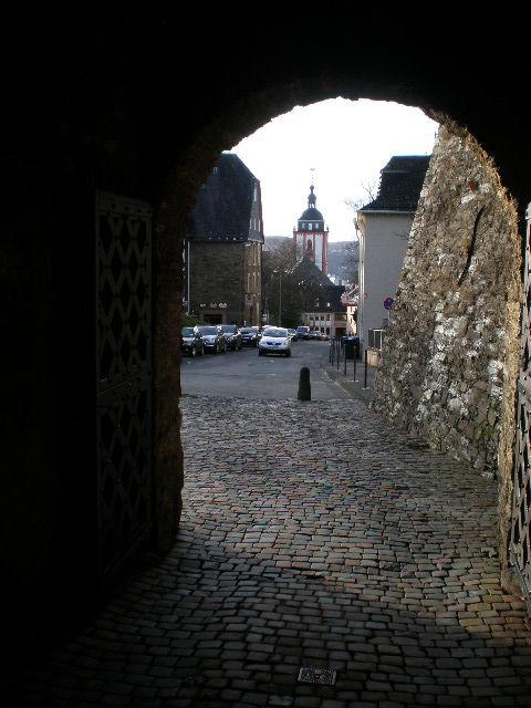 Blick durch den Torbogen des Oberen Schlosses auf die Burgstrasse. Im Hintergrund ist die Nikolaikirche zu sehen.