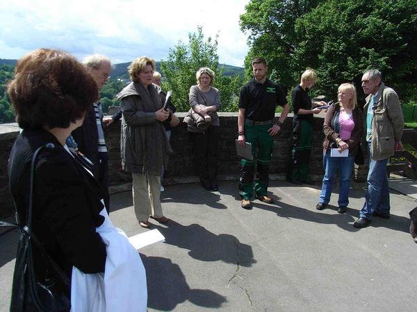 Zu sehen ist eine Gruppe von Gästen während einer Führung, durchgeführt von Mitarbeitern des städtischen Grünflächenamtes und der Stadtführerin Ingrid Heinz. Der Standort befindet sich auf dem kleinen Krebs (alter Wehrturm) mit Blick auf den Lindenberg.