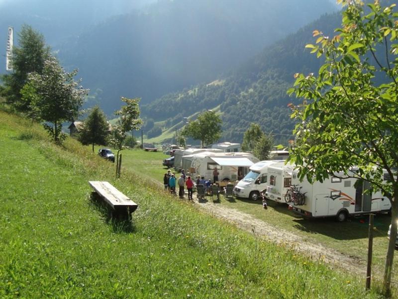 Wohnwagen und eine Bank sond im Vordergrund. Dahinter ein Bergpanorama.