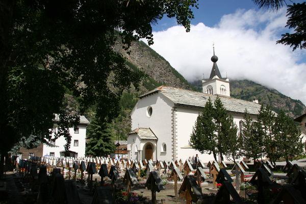 Bei der römisch-katholischen Kirche von Täsch befindet sich auch der Friedhof, wo die Namen der Verstorbenen auf Holzkreuzen zu lesen sind.