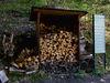 Holzaufbewahrung und Schild mit Informationen.