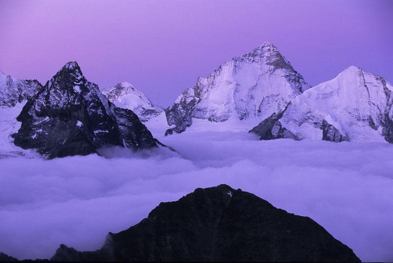 Montagnes dentelées surplombant la mer de brouillard, peu avant le lever du soleil: Dent d'Hérens (gauche), Zinalrothorn (centre) et Dent Blanche.