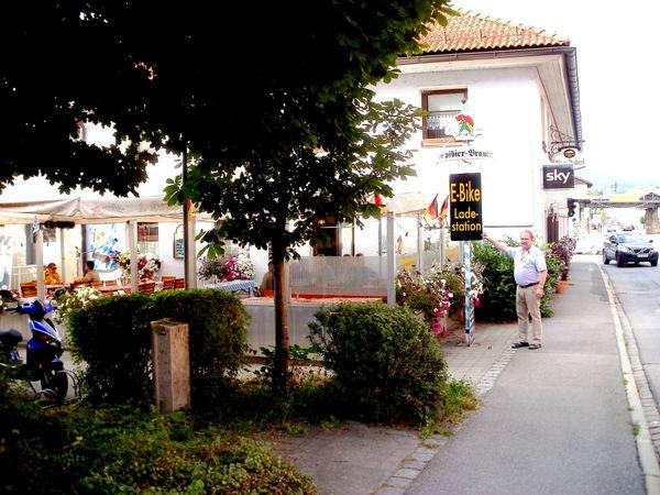 Der Wirt Rudi Eichinger vor dem Schild der E-Tankstelle im Biergarten des Bräustüberl Zwiesel